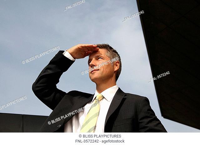 Businessman outdoors looking around