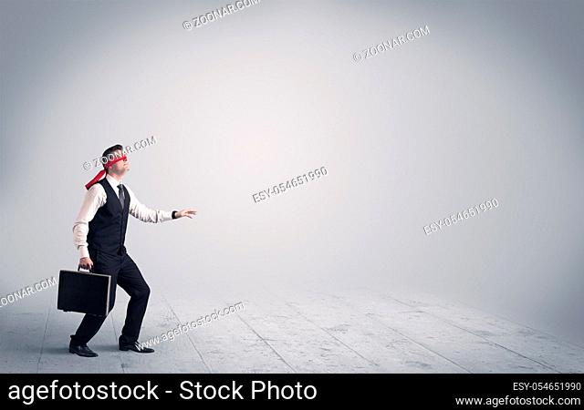 A young male business person in elegant dress standing with red blindfolds in a clear, empty space concept