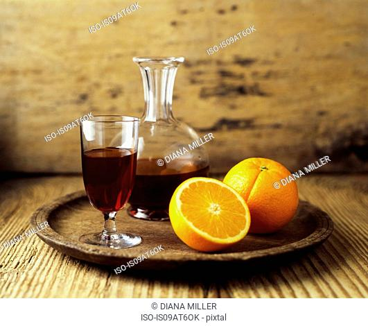 Still life of red wine decanter and fresh orange fruit