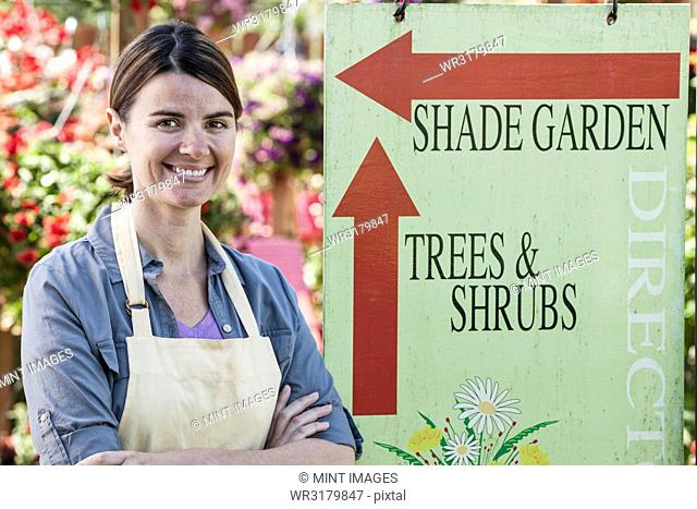 Young Caucasian woman employee of a garden centre nursery standing by an information sign