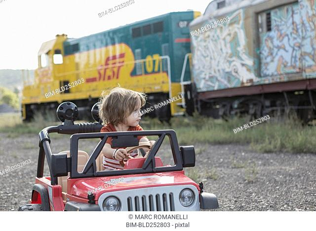 Caucasian boy driving toy car near train