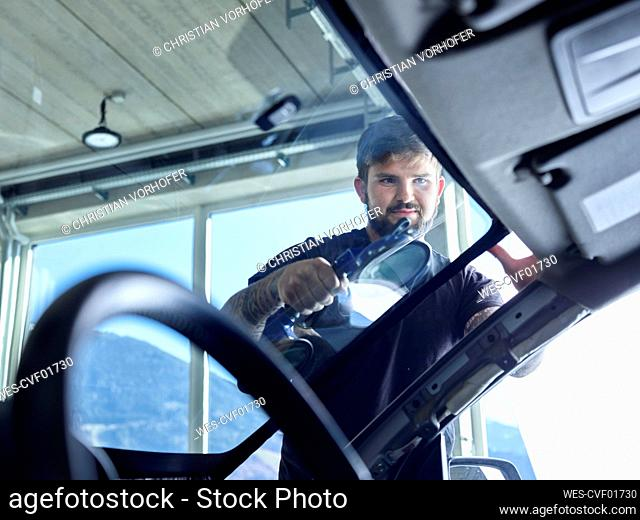 Repairman cleaning windshield of car at garage
