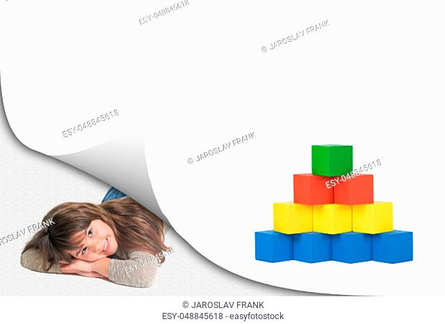 Blank white page with curl effect and smiling cute little girl lying in an exposed corner looking at the camera. Blank page and a pyramid created from colorful...