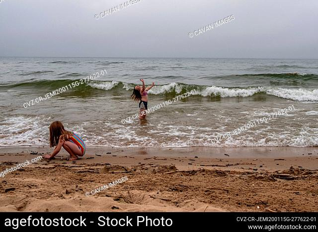 girls playing on beach on a cloudy summer day