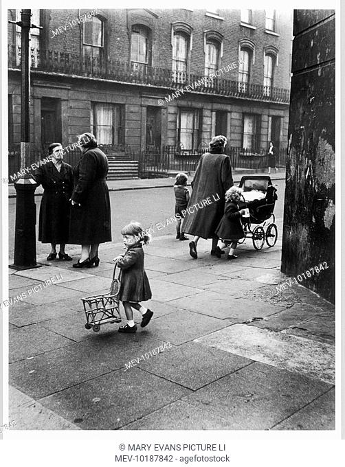 A little girl turns to look back down the road on the corner of Southam Street, North Kensington, London as  two older ladies stop to talk below a streetlamp