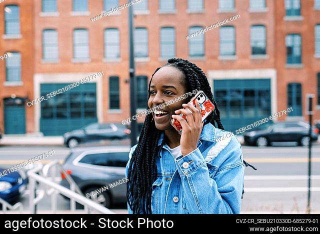 Young black woman using her phone for a call with city surrounding