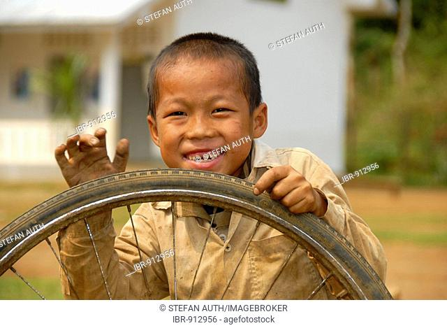 Grinning child playing with an old tyre in front of a school, Khmu People village near Luang Prabang, Laos, Southeast Asia