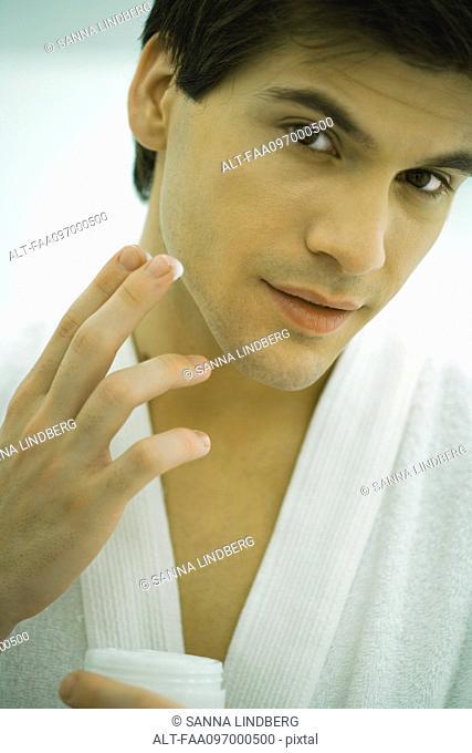 Man in bathrobe moisturizing face