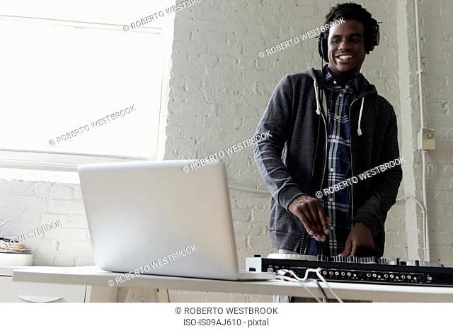 DJ using laptop and mixing desk