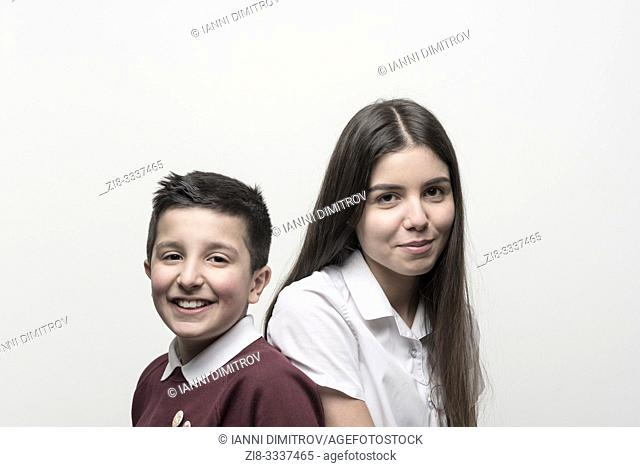 UK, England, Portrait of 10 years old boy and his teenage sister , both in school unoforms . Studio settings