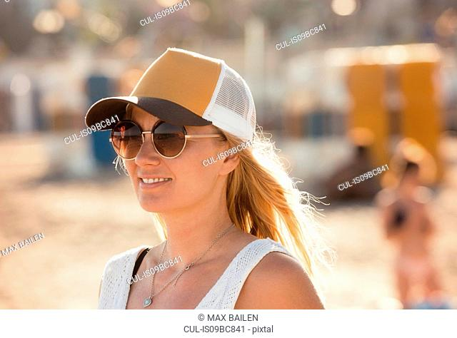 Portrait of woman on beach, wearing sunglasses and cap, Sitges, Catalonia, Spain