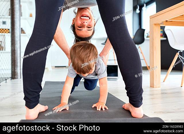 Fröhliche Mutter hilft Kind beim Purzelbaum auf der Turnmatte im Wohnzimmer