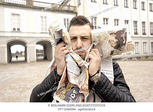 Man assailed by newspapers, in Munich, Germany