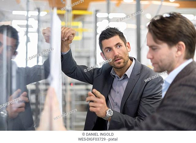 Two businessmen discussing plan in modern factory
