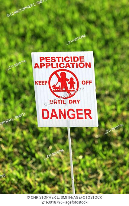 Pesticide Application warning sign on a stick in a lawn in Florida USA