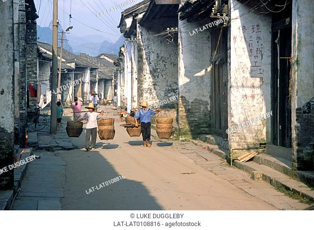 Town. Street. Houses. Electricity cables,wires. Two people carrying large baskets on poles across shoulders