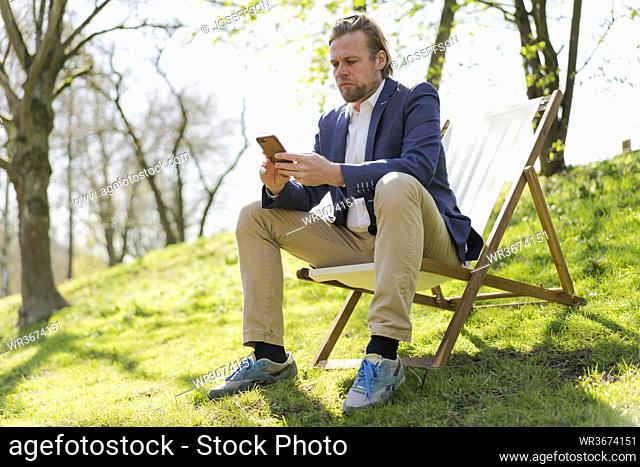 Male entrepreneur using smart phone while sitting on chair at park