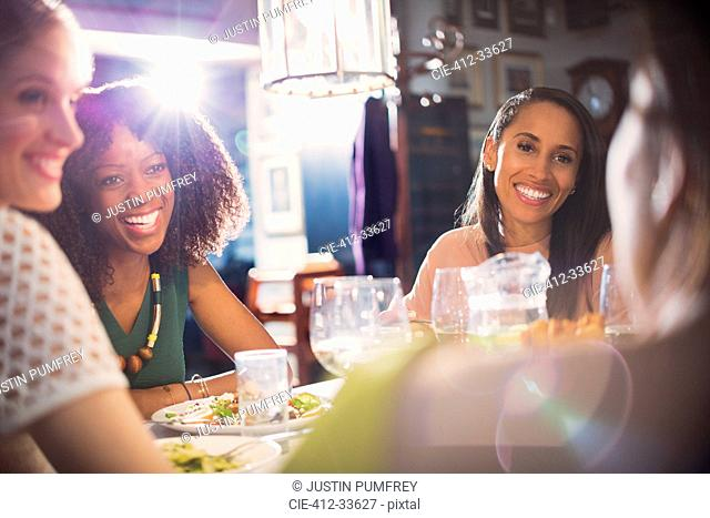 Smiling women friends dining talking at restaurant table