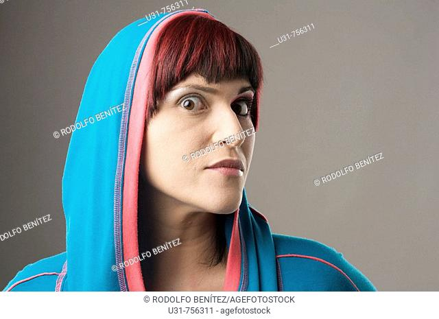 Redhaired trendy girl wearing a hood with makeup on one eye