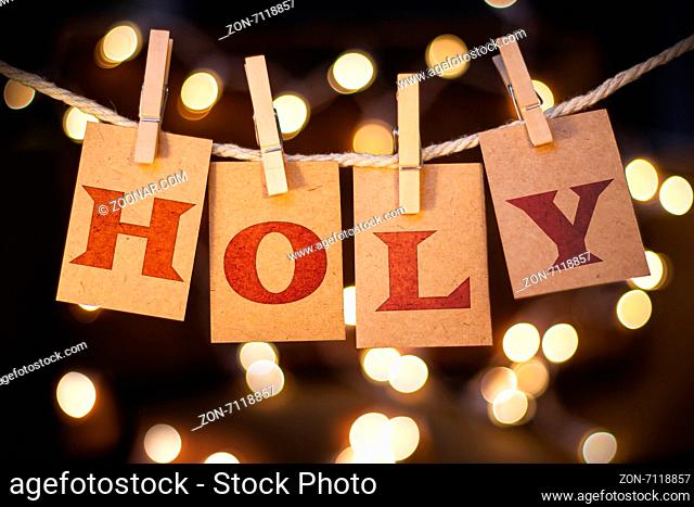 The word HOLY spelled out on clothespin clipped cards in front of glowing lights