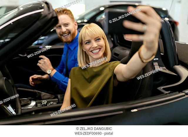 Couple taking selfies, sitting in convertible in car dealership