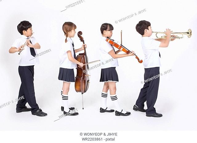 Four elementary students in uniforms standing sideways and playing different musical instrument each
