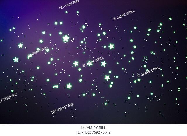 Fluorescent stars on blue background, studio shot