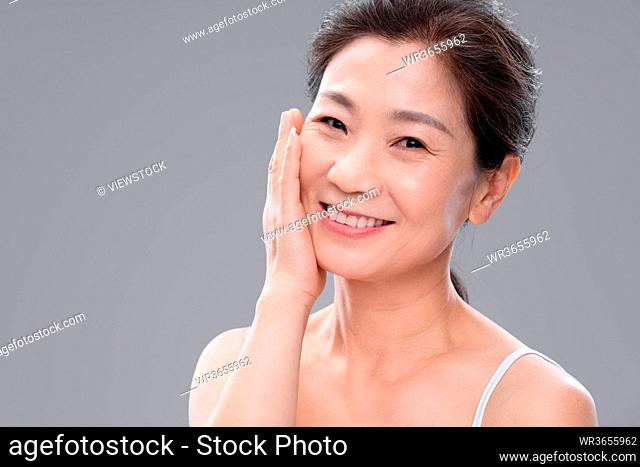 With the hand touch cheeks elegant middle-aged women
