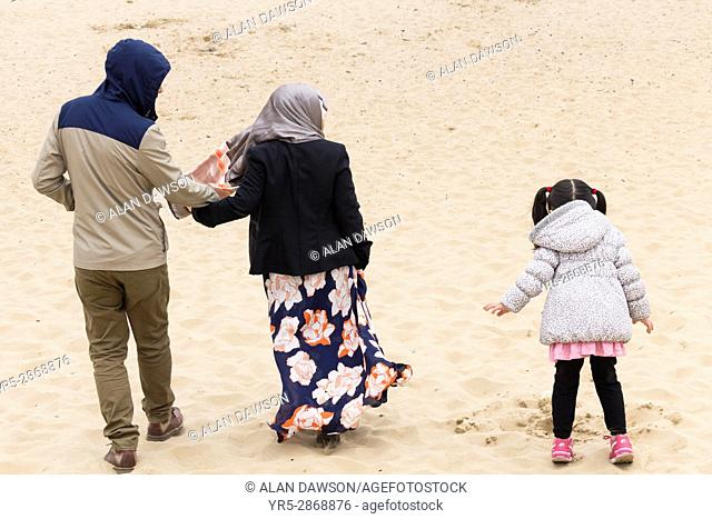 Seaton Carew, County Durham, north east England. United Kingdom. Asian family on the beach on a cold overcast day