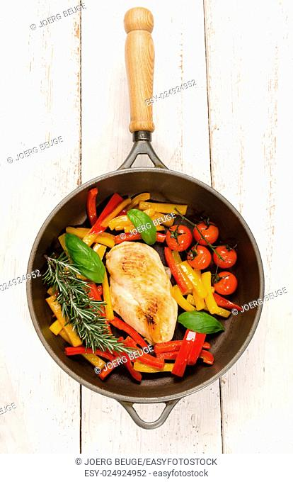 chicken breast filet in a cast iron pan, red and yellow bell pepper, cherry tomato, basil and rosemary