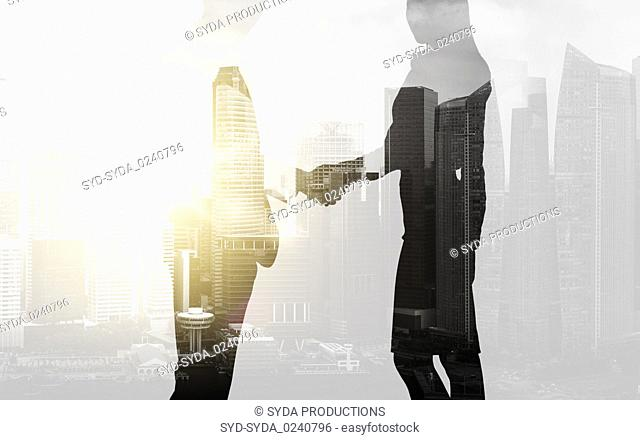 business people shaking hands over city background