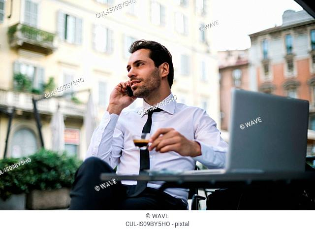 Mid adult businessman at sidewalk cafe table making smartphone call, Milan, Italy
