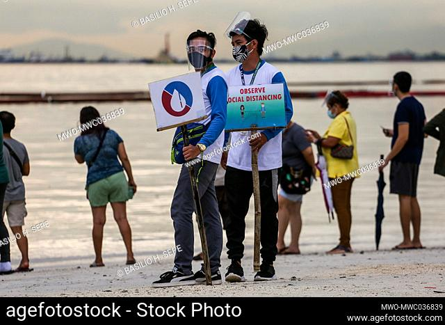 Workers remind people to observe social distancing as people flock to a portion of Manila baywalk area that was covered with crushed dolomite rocks amid rising...