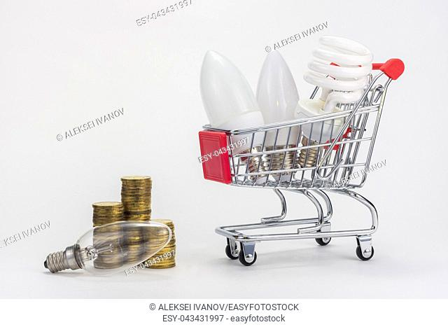 In the grocery cart are LED and energy-saving light bulbs, near the incandescent lamp and stacks of coins