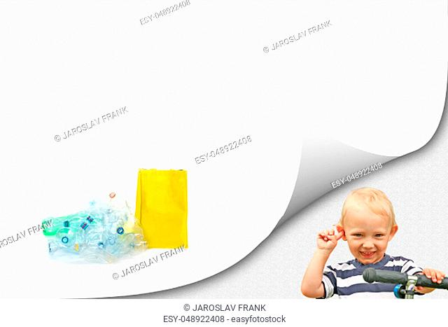 Smiling blond boy is looking at a camera. Pile of plastic waste is lying on the white background. The empty yellow bag is standing next to them