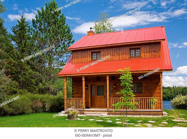 Small cottage style log home facade with red sheet metal roof and brown trim in summer