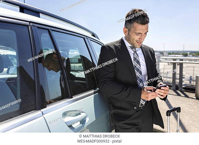 Businessman leaning against car looking at cell phone