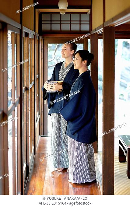 Caucasian woman wearing yukata with Japanese friend at traditional ryokan, Tokyo, Japan
