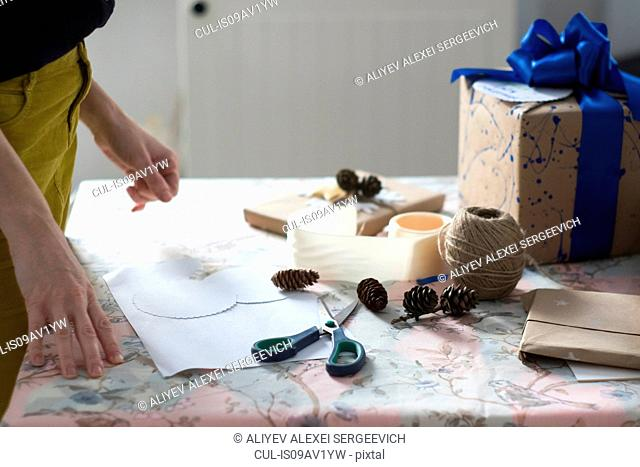 Side view of mid adult woman wrapping gift at table