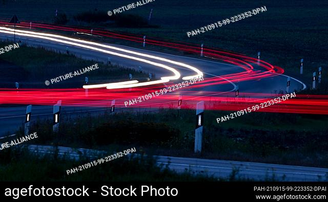 dpatop - 15 September 2021, Saxony, Leipzig: Cars drive in the early morning over a country road at the outskirts of Leipzig