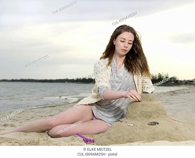 Young woman building sandcastle