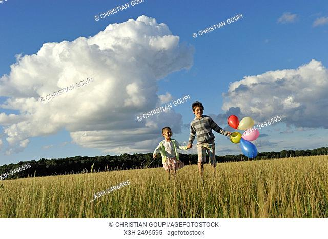 young boy with his sister running with balloons in a field, Ile-de-France, France, Europe