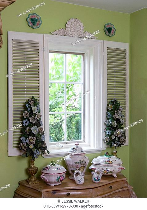 WINDOW TREATMENTS: White stationary shutters are decorative accents around window, architectural accent above, Faience pottery, metal enamel flower trees