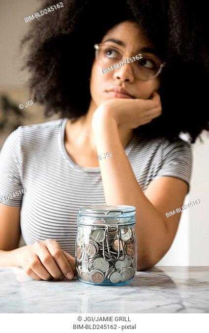 Pensive African American woman with jar full of coins