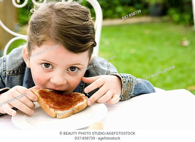 Little girl eating bread with jam