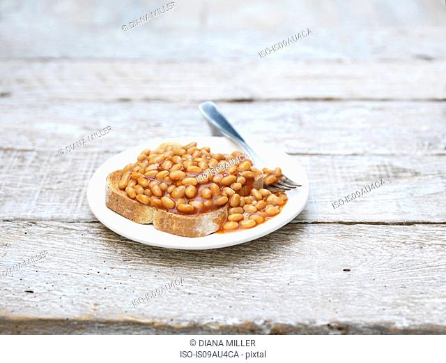 High angle view of baked beans on toast with fork on white plate on whitewashed surface