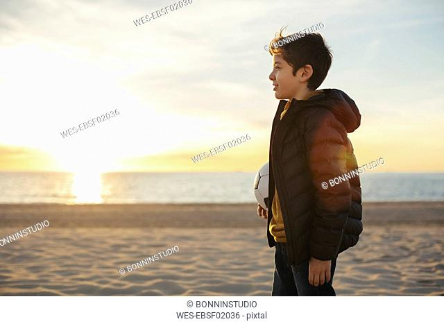 Boy holding football on the beach at sunset
