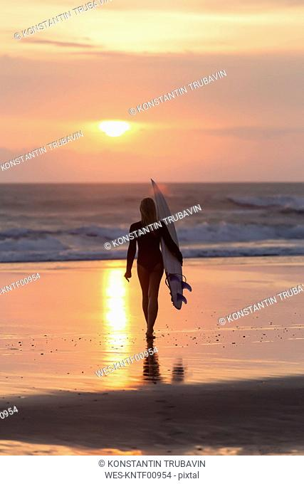Indonesia, Bali, young woman with surfboard at sunset