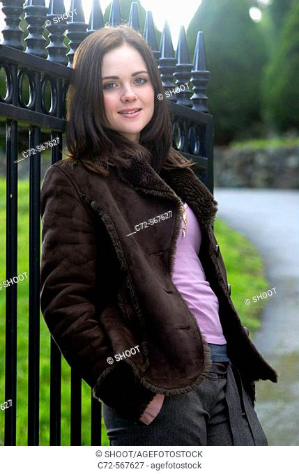 young woman leaning on gate