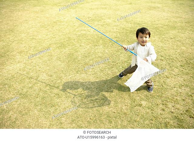 A small boy holding a net stands amidst the ground